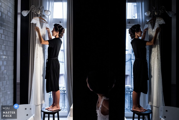 A woman is reflected in the mirror as she hangs the bride's wedding dress in this photo by a Santa Fe, Argentina wedding photographer.