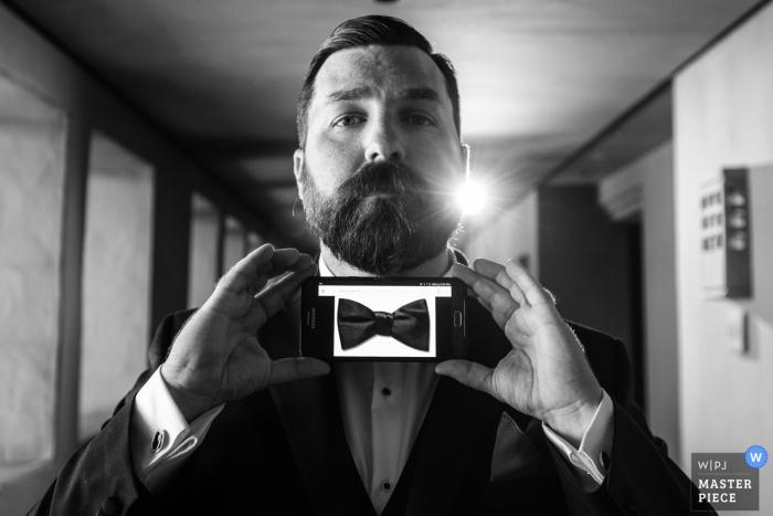 Black and white photo of a man holding a picture of a bow tie on his phone up to his neck by a Madrid, Spain wedding photographer.