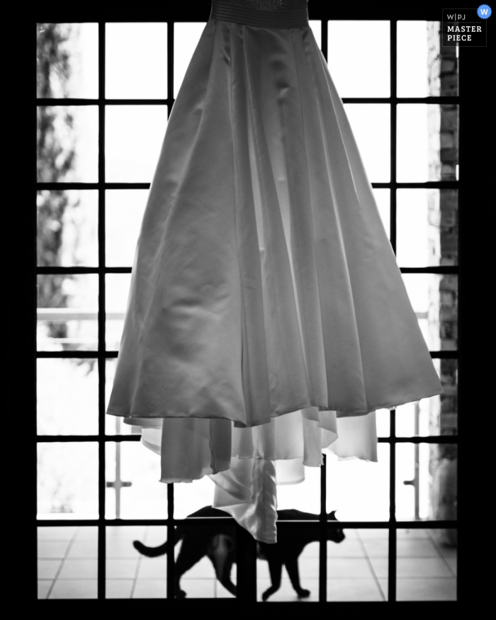 Black and white detail photo of the bride's gown hanging in a window as a cat passes beneath it by a Porto, Portugal wedding photographer.