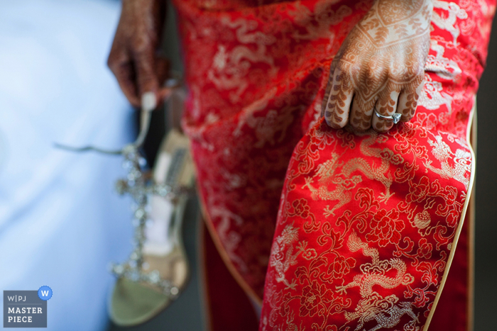 Detail photo of the bride's hand with henna and her wedding ring against her intricate red dress by a San Francisco, CA wedding photographer.
