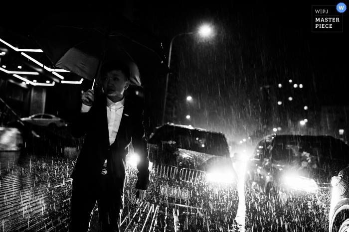 Photo noir et blanc d'un homme debout sous la pluie, la nuit, avec deux véhicules derrière lui, par un photographe de mariage à Guizhou, en Chine.