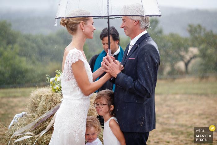 Die Braut, der Bräutigam und zwei junge Mädchen suchen während der Zeremonie in diesem Foto eines Amsterdamer Hochzeitsfotografen Schutz unter einem Regenschirm.