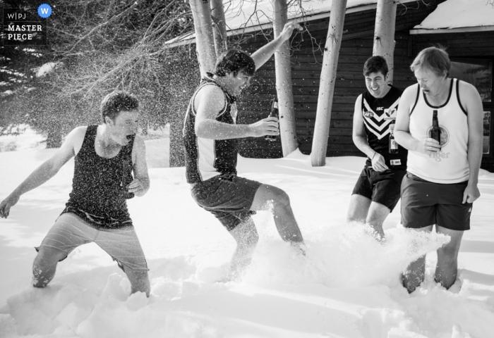 Photo noir et blanc de quatre hommes en short buvant de la bière à l'extérieur sous la neige, par un photographe de mariage du Montana.