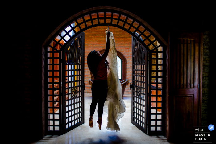 Photo of a woman jumping in the air to hang the bride's gown above a doorway by a Charleston, SC wedding photographer.