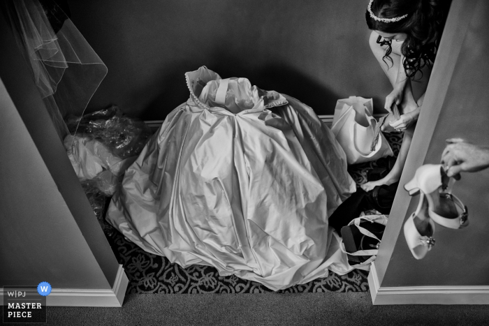 Black and white photo of the bride's dress on the floor ready for her to step into as a woman hands the bride her heels by a Charleston, SC wedding photographer.