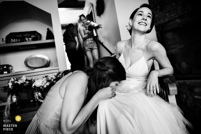 Black and white photo of a woman fixing the bride's wedding dress by a Burlington, VT wedding photographer.