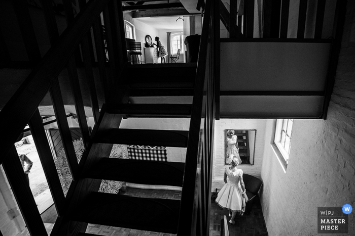 Black and white photo of the bride checking herself in a mirror downstairs as another woman gets ready upstairs by a Lower Saxony, Germany wedding photographer.