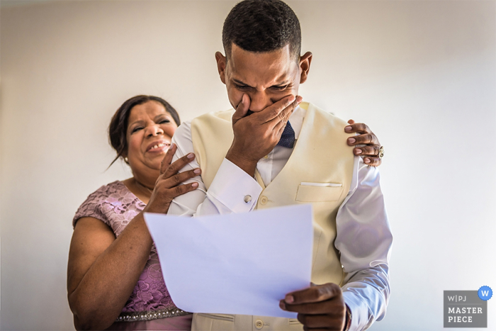 Photo of a woman holding the groom as he tears up reading a letter - Image by a Barcelona wedding photographer.