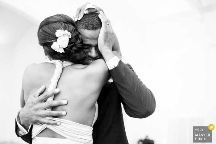 Black and white photo of the bride and groom hugging by a Raleigh, NC wedding photographer.