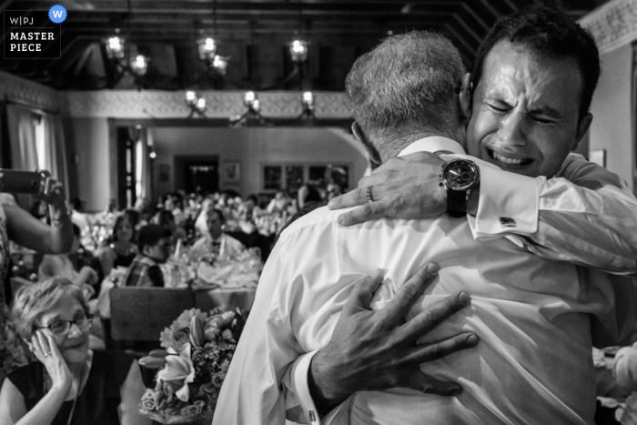 Black and white photo of the groom hugging an older man during the reception by an Alicante, Valencia wedding photographer.