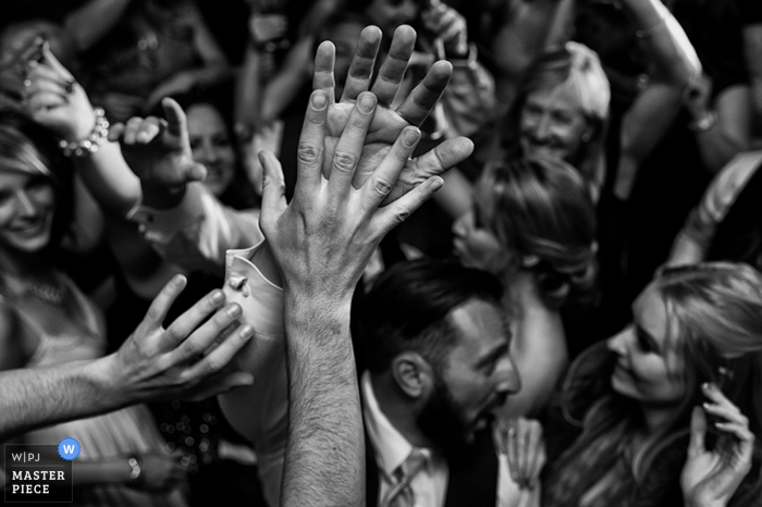 Black and white detail photo of a crowd people raising their hands and high-fiving by a Carson City, NV wedding photographer.
