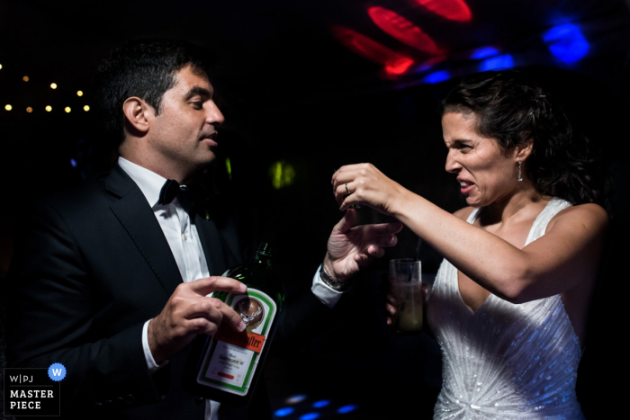 Photo of the bride making a face as the groom hands her a glass of Jagermeister by a Santa Fe, Argentina wedding photographer.