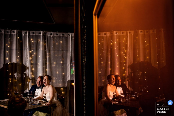 The bride and groom are reflected in a mirror as they laugh during a speech in this photo by a Chicago, IL wedding photographer.