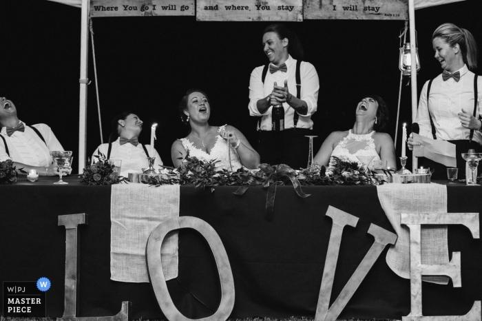 Foto en blanco y negro de la novia y los invitados riendo durante un discurso de un fotógrafo de bodas en Knoxville, TN.