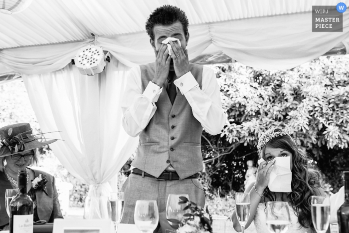 Black and white photo of the bride and groom getting tearful during a speech by a Bristol, England wedding reportage photographer.