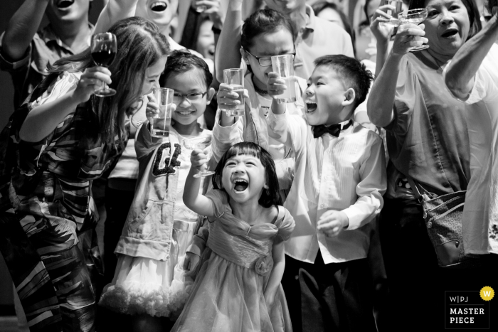 Black and white photo of children holding up their glasses during a toast by a Malaysia wedding photographer.