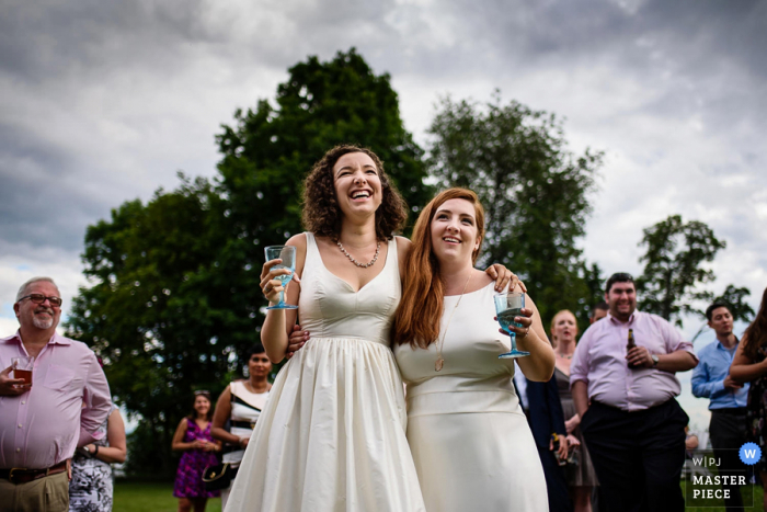 Two women stand with their arms around each other's shoulders as they hold their drinks in this photo by a Burlington, VT wedding photographer.
