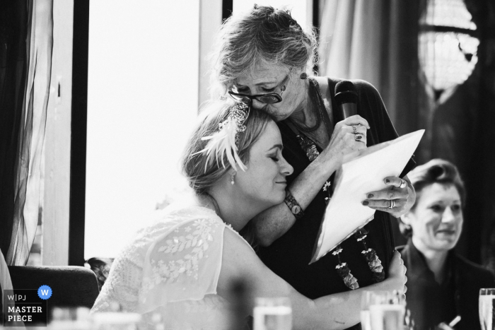 Black and white photo of a woman kissing the bride's head during her speech by a Greater Manchester, England wedding reportage photographer.
