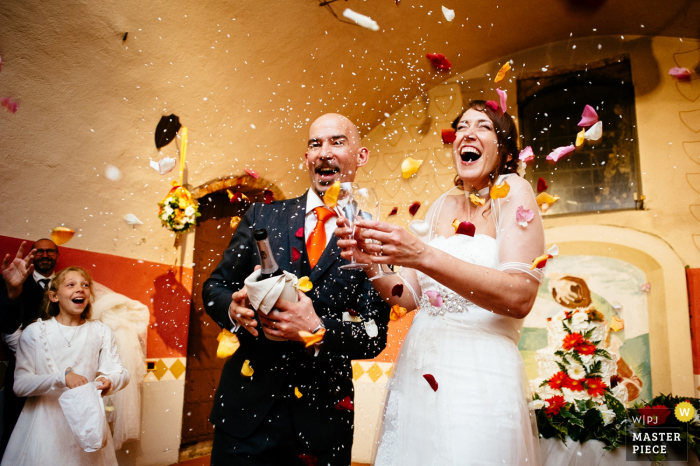 The bride and groom hold champagne and two glasses as guests toss rice and flower petals in this photo by a Rome wedding photographer.