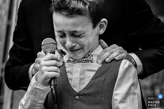 A young boy gets emotional during the speech in this black and white photo by a Paris wedding photographer.