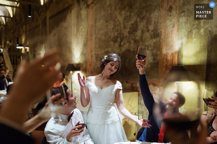 A bride stands among the wedding guests as they toast her in this photo by a Rome wedding photographer.