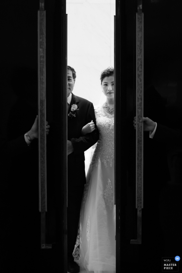 Shanghai wedding photographer captured this black and white image of the church doors opening and revealing the first glimpse of the bride before she walks down the aisle