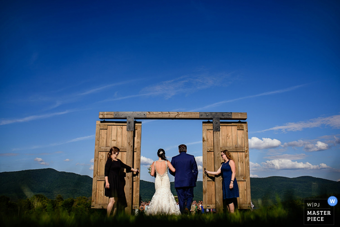 The bride and groom walk through a doorway in an open field in this photo by a Burlington, VT wedding photographer.