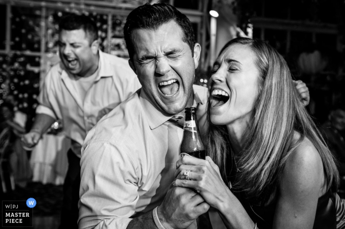 Black and white photo of two guests singing as they pretend to use a bottle as a microphone by a New Jersey wedding photographer.