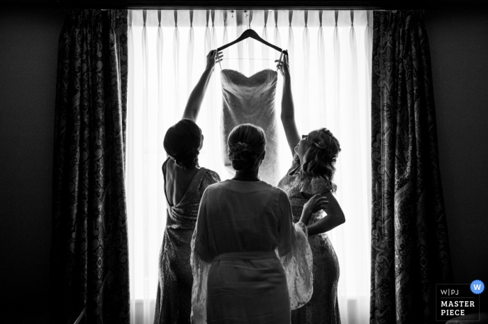 Black and white photo of two bridesmaids preparing to help the bride into her wedding gown by a Houston, TX wedding photographer.