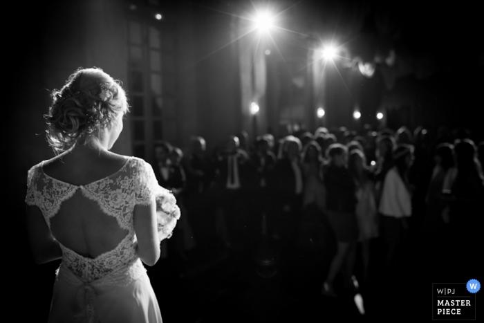 Foto en blanco y negro de la novia de pie frente a sus invitados, con luces que emiten un fotógrafo de bodas en París, Francia.