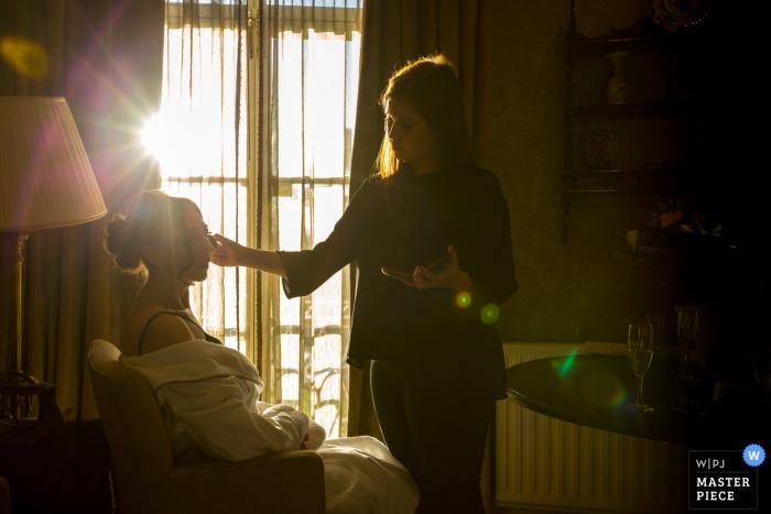 La novia se sienta para maquillarse mientras el sol brilla a través de la ventana en esta foto por un fotógrafo de reportajes de bodas en Essex, Inglaterra.
