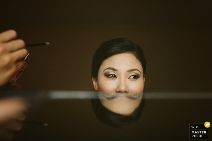 Photo of a woman peeking over a reflective surface by a Tuscany wedding photographer.