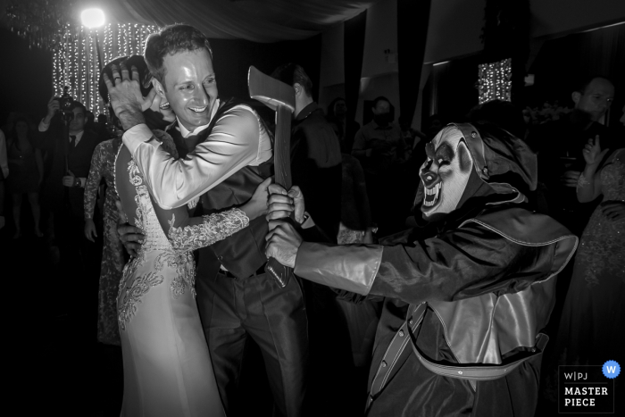 The groom shields his bride from a fake ax in this black and white photo by a Santa Catarina, Brazil wedding photographer.