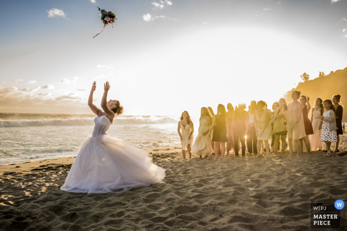 The bride and guests stand on a sunny beach as she tosses her bouquet over her head in this photo by a Geneva, Switzerland wedding photographer.