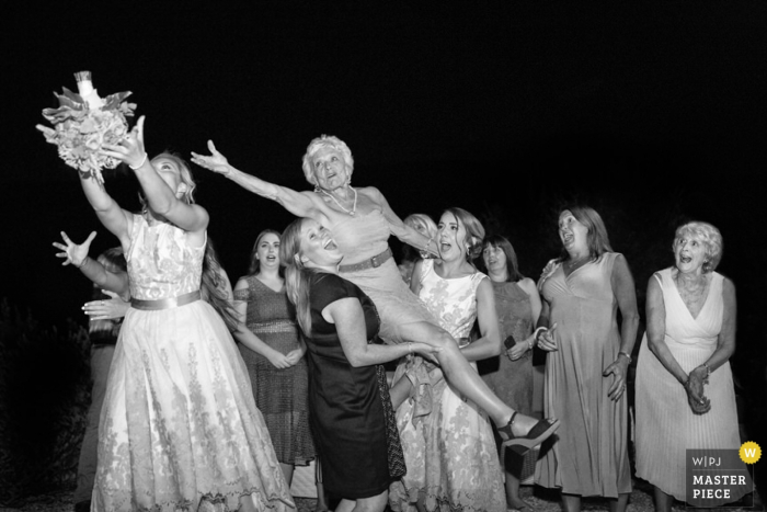 A woman is lifted by two others as she and another guest try to catch the bouquet in this black and white photo by a Tuscany wedding photographer.
