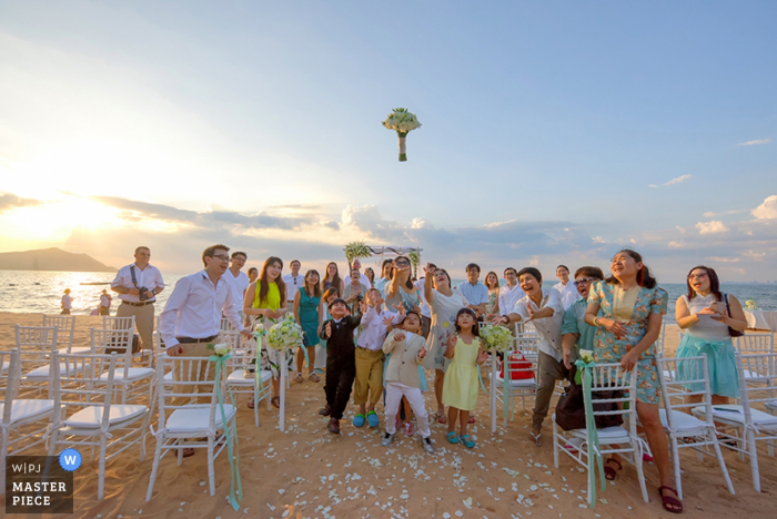Photo of the wedding guests trying to catch the bride's bouquet as it hangs in the air by a Bangkok, Thailand wedding photographer.