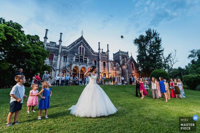 The bride tosses her bouquet on a large lawn in front of a stately building in this photo by a Venice wedding photographer.
