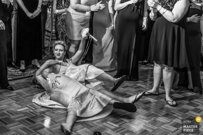 Two guests find themselves on the floor during the bouquet toss in this black and white photo by a Detroit, MI wedding photographer.
