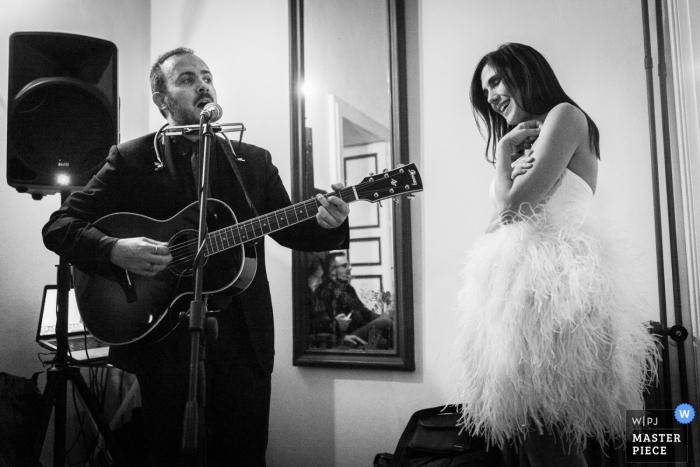 De bruid wordt toegezongen door een man die gitaar zingt en bespeelt in deze zwart-witfoto door een trouwfotograaf uit Calabrië.