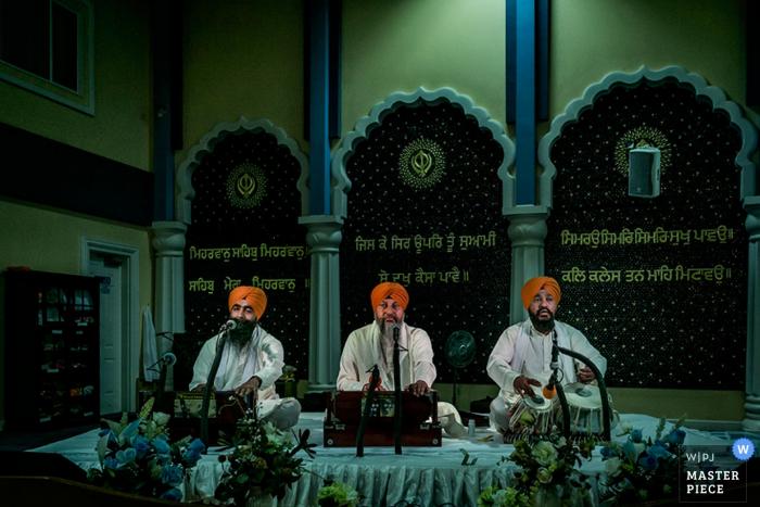 Foto van drie musici die op een platform door een het huwelijksfotograaf van Toronto presteren.