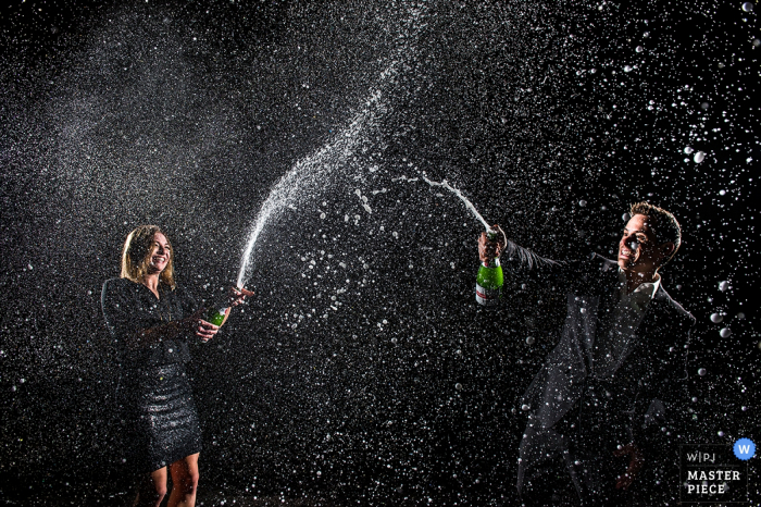 Boulder wedding photographer captured this silly photo of a bride and groom showering each other with champagne