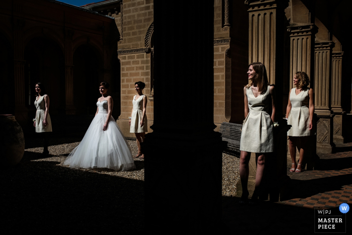 Lyon wedding photographer captured this image of the bride and bridesmaids posing in a column filled room