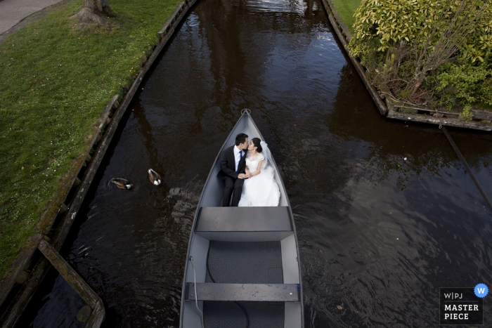 North Rhine wedding photographer captured this aerial image of a bride and groom riding in a row boat while ducks swim nearby