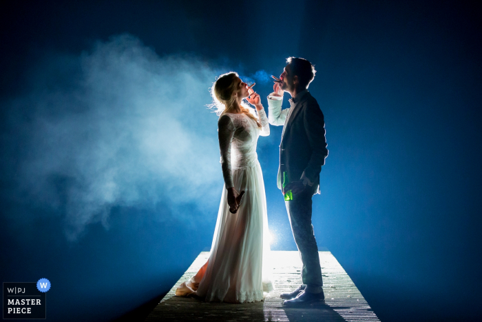 Holland wedding photographer captured this picture of a bride and groom smoking on a platform with a spotlight behind them
