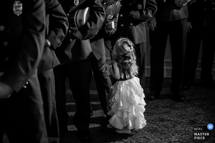 El fotógrafo de bodas de Nueva Jersey capturó esta imagen en blanco y negro de una niña con un vestido blanco mirando a los policías que la rodean.