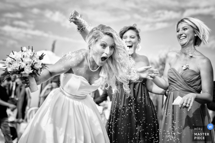 This silly black and white photograph of a surprised bride getting rice poured on her back was captured by a Tuscany wedding photographer