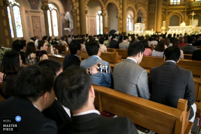 El fotógrafo de bodas de Londres creó esta imagen desde la parte posterior de la iglesia, mirando a los invitados a la boda mientras que algunos toman selfies