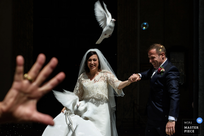 El fotógrafo de bodas de Roma capturó esta imagen de una feliz novia y el novio saliendo de la ceremonia mientras liberaban a una paloma