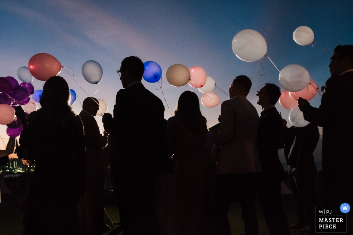 Dubai wedding photographer captured this image of wedding guests holding balloons outside at sunset