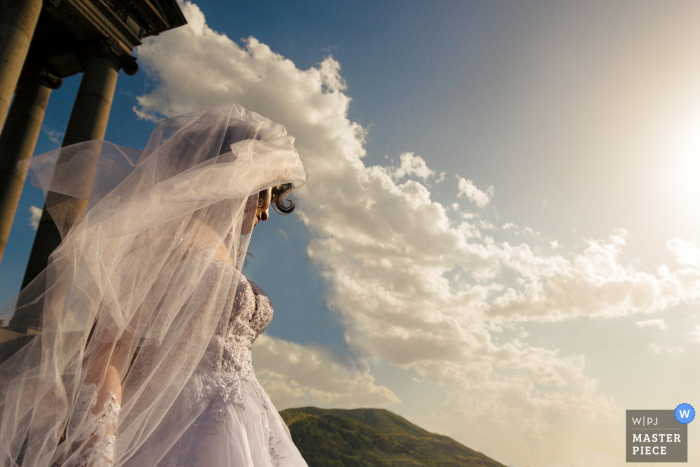 Armenia wedding photographer captured this bridal image while she stands under a blue sky filled with white clouds that look like they are part of her dress